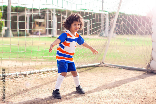 Obraz Little boy plays football outdoor. Children and lifestyle concept - fototapety do salonu