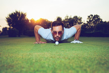 Man Blowing On Golf Ball