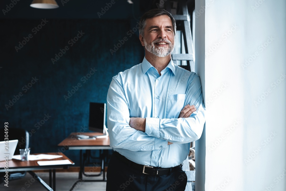 Fototapety, obrazy: Mature businessman in a corporate suit standing in office and looking away through large windows optimistically.