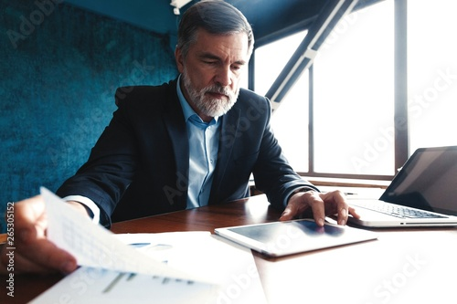 Aluminium Prints Equestrian Serious mature financial advisor sitting at the table and checking financial report using digital tablet at office.