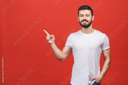 Fotografía  Look over there! Happy young handsome man in casual pointing away and smiling while standing against red background