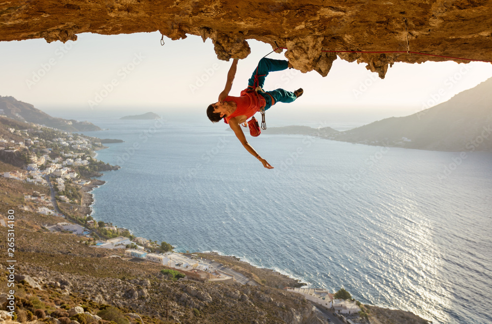 Fototapety, obrazy: Male rock climber on challenging route going along ceiling in cave