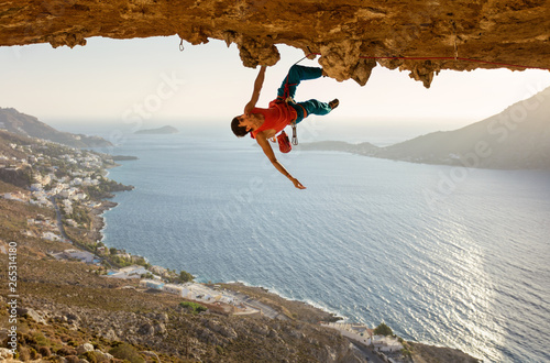Fotografía  Male rock climber on challenging route going along ceiling in cave