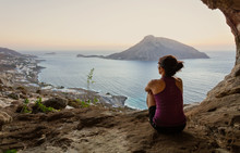 Female Climber Sitting In Cave And Watching Sunset