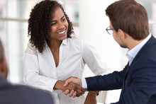 Smiling Diverse Businesswoman And Businessman Handshake Make Deal At Meeting