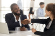 Leinwandbild Motiv Happy african manager broker handshaking caucasian client at meeting