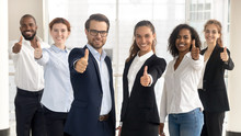 Business Leaders With Employees Showing Thumbs Up Looking At Camera