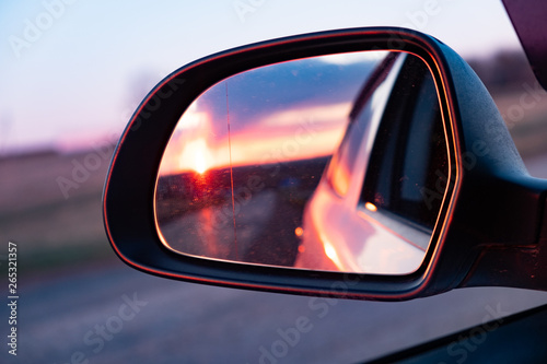 The reflection of the setting sun in the rearview mirror of the car Wallpaper Mural