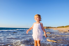 Portrait Of Cute Little Adorable Toddler Girl In White Clothes Walking On The Empty Beach On A Warm Sunny Summer Day. Holidays At Sea. Family Vacation. Selective Focus, Space For Text.