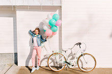 Full-length Portrait Of Active Cheerful Girl With Party Balloons Ready To Bike Ride In Sunny Morning. Stylish Young Woman Wearing Pink Clothes And Sneakers Posing Outside Next To Bicycle After Event