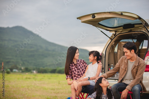 Fototapeta Happy little girl  with asian family sitting in the car for enjoying road trip a
