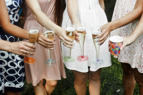 Fotografija hands of woman holding colorful glasses and toasting champagne at joyful party i