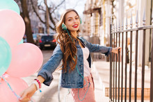 Stylish Positive Girl Walking Down The Street With Bunch Of Colorful Balloons And Clings To The Iron Fence. Charming Young Woman With Long Hair In Retro Jacket Having Fun Outside Going To The Party