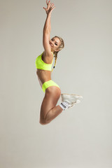 Muscular young woman posing in sportswear against grey background. Fit female model with perfect torso in studio.