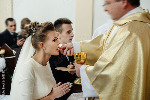 Photo bride and groom having communion with priest on knees at wedding ceremony in chu