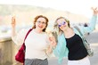 Attractive blond woman in sun glasses walking downtown and eating ice cream - carefree women
