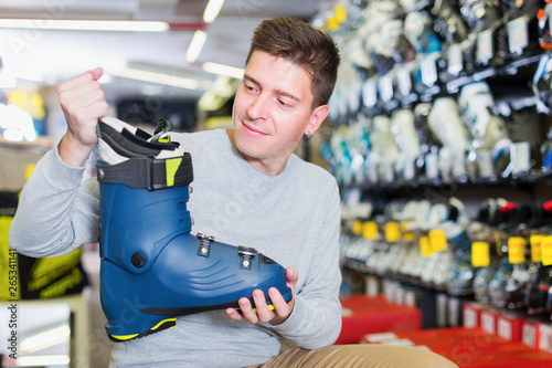 Fototapety, obrazy: Customer male is trying on new boots for skiing