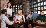 Female owner of rustic restaurant serving guests