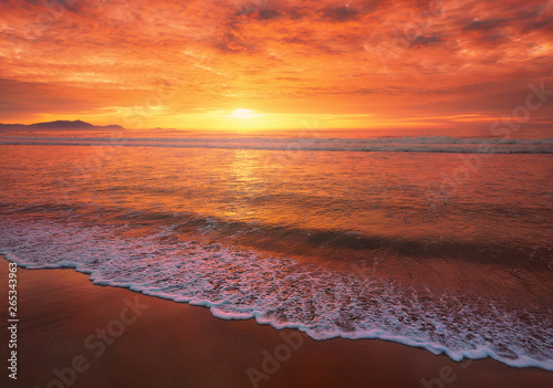 obraz lub plakat beautiful red sunset on beach with a wave on the shore