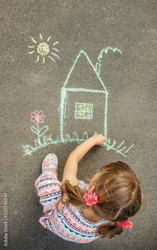 The child draws the house with chalk on the asphalt. Selective focus. - fototapety na wymiar