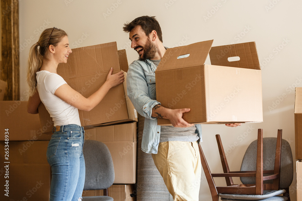 Fototapety, obrazy: Young couple carrying big cardboard box into new home.Moving house.