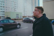Man standing in yard of city Portrait of young man in casual clothes standing beside cars in yard of high-rise buildings