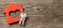 Wooden Red House And Keys On The Old Wooden Boards. Copy Space For Text.