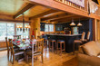 Set Wooden Dining Table With High-Back Tan Leather Padded Sitting Chairs And Kitchen With Black Cabinets, Island With Granite Countertop And Leather Padded Barstools And High-Back Sitting Chairs Inside A Milled Cottage Style Flat Log Profile Home; Quebec, Canada