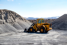 Wide Angle View Of A Large Wheel Loader Heavy Equipment Machine Parked In Front Of A Gravel Pile In The Mountain Landscape; Iceland