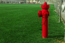 Red Fire Metal Hydrant Stands On Green Grass, Copy Space