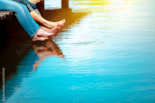 Romantic couple man and woman are sitting on a dock with barefoot feet dangling in pond water. Sunny weather. Happiness, vacation, summer, concept. Copy space for text.