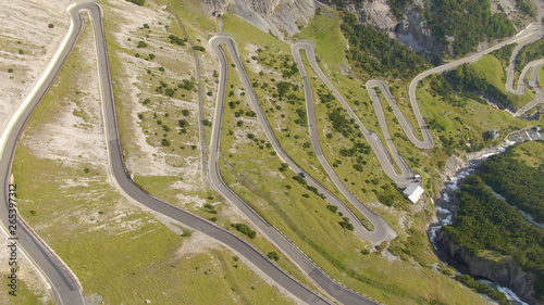 Fototapeta AERIAL: Flying above a scenic switchback road leading up to a mountain pass. obraz na płótnie