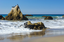 El Matador Beach In Malibu California With Waves Washing Over A Rock In The Foreground And Blue Skies With Shorebirds On A Rock.