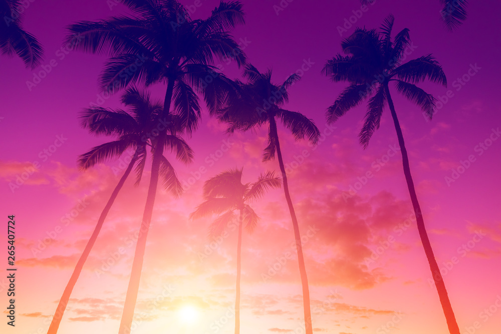 Fototapeta Tropical island sunset with silhouette of palm trees, hot summer day vacation background, golden sky with sun setting over horizon
