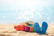 Beach accessories straw hat, flip flops, towel on sunny tropical beach, summer holidays
