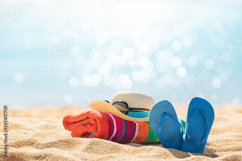 Fototapeta Beach accessories straw hat, flip flops, towel on sunny tropical beach, summer h