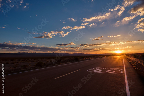 Spoed Fotobehang Route 66 Route 66 pavement sign in the foreground and the diminishing perspective of the road leading to a dramatic sunset in the Mojave desert outside of Amboy, California.