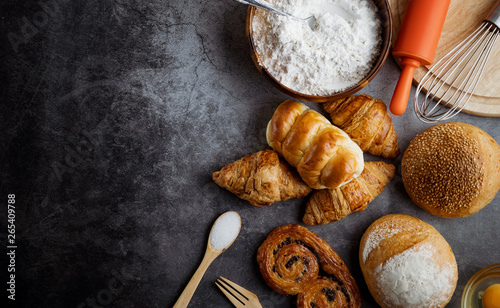 Freshly baked bread on wooden table,Bakery Concept- gold rustic crusty loaves of bread and buns on black chalkboard background. captured from above (top view, flat lay. Layout with copy space