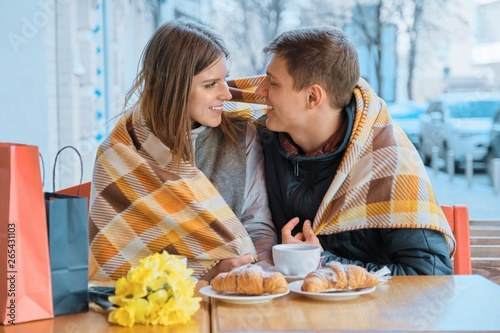 Young couple in love in outdoor cafe under plaid, spring yellow bouquet on the table, coffee, croissants Canvas-taulu