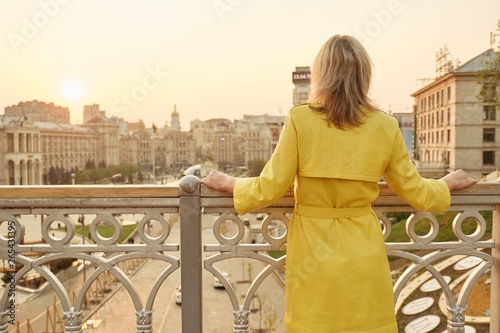 Rear view of woman looking at panorama of evening city. Adult female in yellow raincoat outdoor, copy space, golden hour