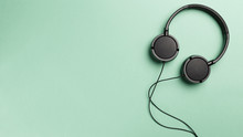 Black Headphones On Mint Background. Headphones On A Pastel Background. Flat Lay Top View Copy Space. Minimal Style With Colorful Paper Backdrop. Music Concept. Neo Mint Color Of The Year 2020