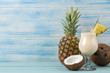 Leinwandbild Motiv Cocktail Pina Colada. Pina Colada refreshing summer alcoholic cocktail with coconut milk and pineapple juice nearby. summer drink. cocktail preparation. on blue wooden background. space for text