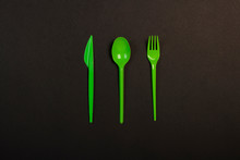 Green Disposable Plastic Tableware And Appliances For The Food On A Black Background. Fork, Spoon And Knife. Concept Plastic, Harmful, Environmental Pollution, Stop Plastic. Flat Lay, Top View.