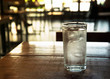 clear glass of cold ice water on brown wood table with blur bar and restaurant background