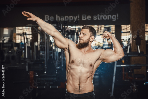 Photo Good looking young man bodybuilder posing in front of the mirror shows big biceps at the gym darkened slogan background