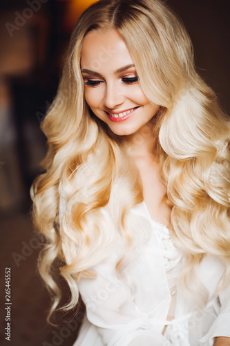 Portrait of gorgeous and sensuality blondie bride posing in bedroom, dreaming and smiling Canvas Print
