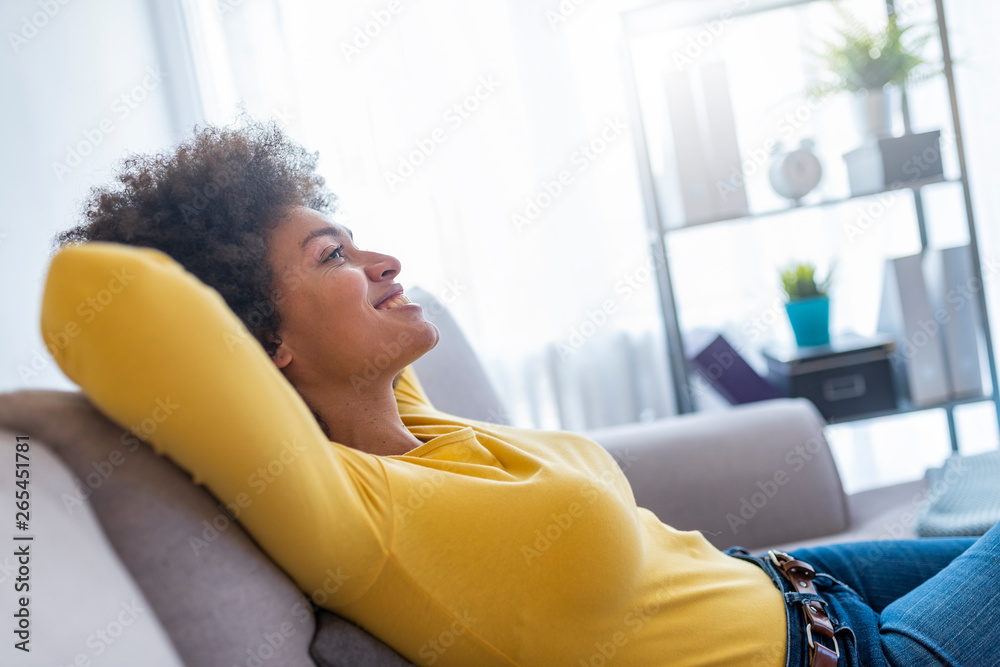 Fototapety, obrazy: Happy woman relaxing on comfortable soft sofa enjoying stress free weekend at home, calm satisfied girl stretching on couch thinking of pleasant lazy day, dreaming and planning sunday morning