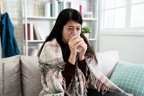 japanese beautiful woman wrapped in warm blanket holding drinking glass of water freezing sitting on sofa at home Tablou Canvas