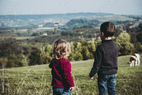 Poster de jardin Vache Deux jeunes enfants en train de regarder des vaches dans un champ