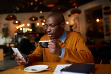 Warm Toned Portrait Of Contemporary African-American Man Using Smartphone Sitting At Table In Coffee Shop, Copy Space